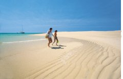 Couple walking on a remote sand cay on the Great Barrier Reef
