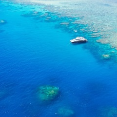 Aerial view of Great Barrier Reef Charter boat at anchor on a reef