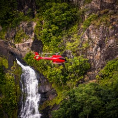 Helicopter Flying with Waterfalls in Background