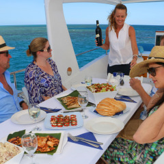 Host serving lunch on private charter boat in Port Douglas