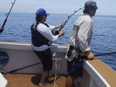 men reeling in fish mission beach