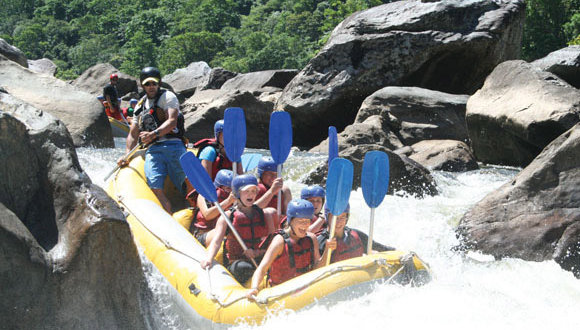 Paddles up and wave at the camera | Tully River white water rafting
