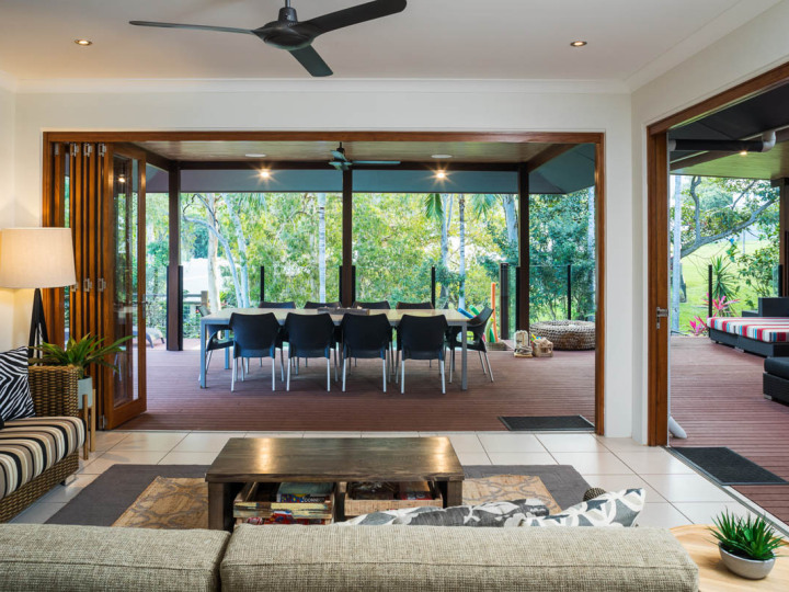 Open plan living area flows out to large outdoor deck and swimming pool | Palm Cove Holiday Home