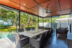 Relax on the poolside patio with outdoor dining and beach views | Bramston Beach Holiday Home