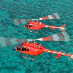 Twin helicopters flying over the Great Barrier Reef